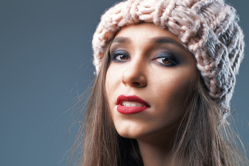 Closeup beauty portrait of a young beautiful caucasian white girl with makeup in pink thick knitted hat on grey background