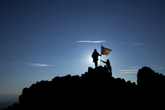 Two soldiers raise the Afghan flag on a mountain top