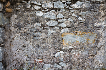 Surface of old stone wall of a medieval fortress. Closeup natural background.  Rough outdoor stone wall texture.