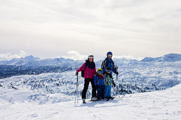 Young happy family with two childrens, boy brothers, skiing in A