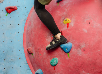 Foot with shoes of female climber on artificial boulder wall at gym