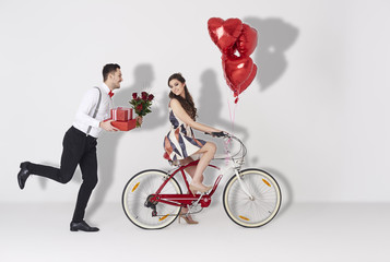 Happy couple with gift and heart shaped balloon