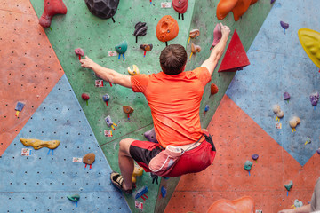 Sport man exercising on artificial climbing wall, modern leisure concept