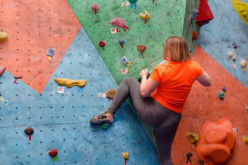 Unrecognizable fat woman in a bad physical shape has been climbing in gym