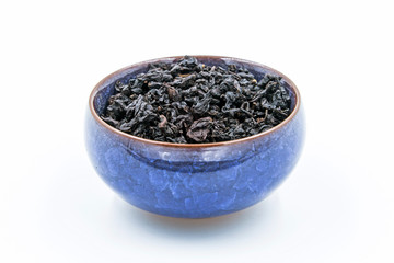 Chinese Oolong Dark Red tea (Black Tie Guan Yin) in a blue ceramic bowl