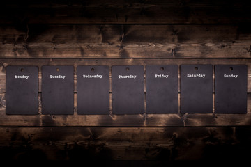 Seven day black chalkboard notices empty and individually hanging from a rustic wooden wall