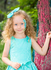 Beautiful happy girl kid with aqua make-up on birthday in park. Celebration concept and childhood, love