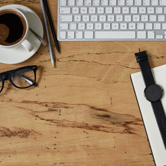 Top view of a style office working desk. Wooden table with a keyboard, a cup of coffee, eye glasses, watch and office tools with copy space, flat lay