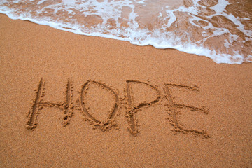 "written words "" hope "" on sand of beach with wave on background"