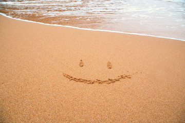 painted smile on sand of beach with wave on background
