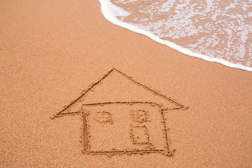 painted home on sand of beach with wave on background