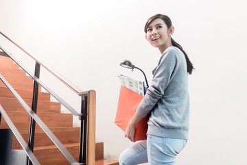 Young Indonesian girl carrying removal crate up the stairs