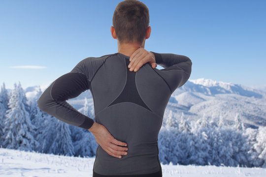 Sport injury, Man with back, neck pain. Pain relief concept in winter background.