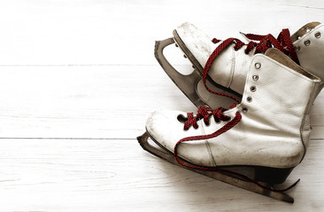 Old white skates for figure skating on a wooden surface