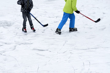 A group of children playing ice hockey at the skating rink outside in winter.