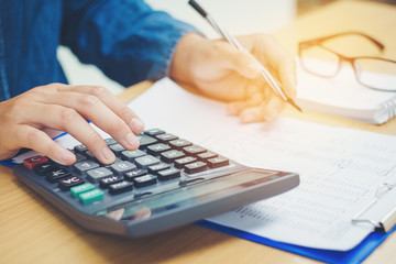 Financial data analyzing hand writing and counting on calculator