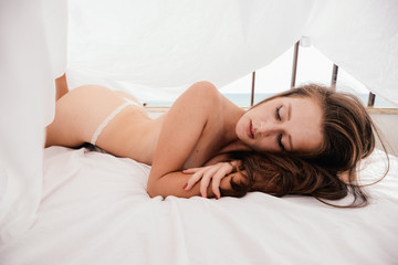 Hiding woman relaxing in bed over light background copy space