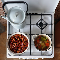 White stove with a pot of stewed fruit, vegetable soup and kettle. View from above.