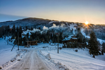 winter landscape in mountainous rural area at sunset