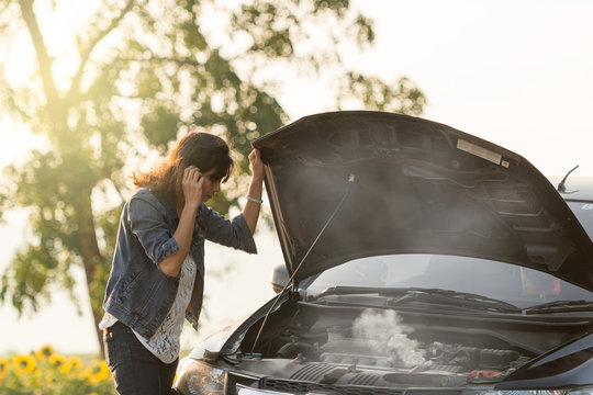 sad woman standing on the road by the broken car in the middle of nowhere. smoke coming out the engine. Help needed. Car service. Tow service.