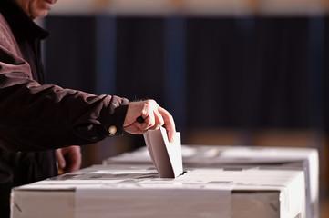 Person casting vote into ballot box