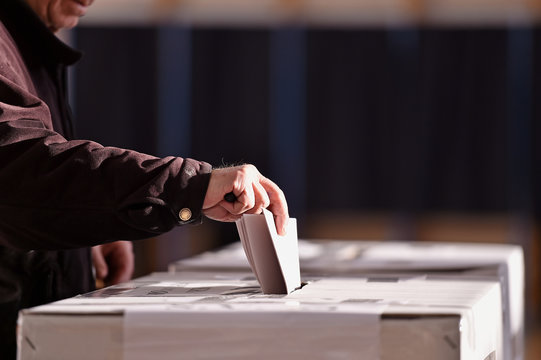 Person casting vote into ballot box