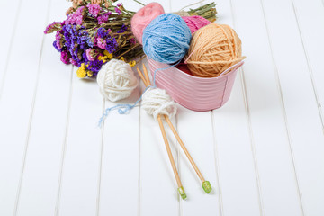 Knitting yarn balls and needles on white wooden background.