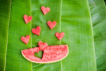 Piece of watermelon and hearts at the background of banana leaves. Flat lay