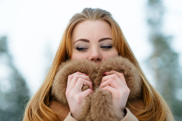 charming woman with fur covers face