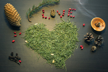 Word Love and heart made out from pine tree needles and other holiday decorations on a table top view.