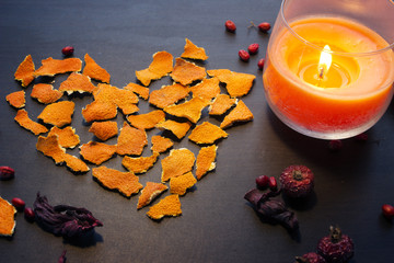 Greeting decor for Valentines Day: Heart made from dry orange peel, candle and dry berries.
