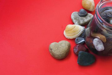 Heart shaped stone, shell and some sea pebble on a red background. Place for greening text.