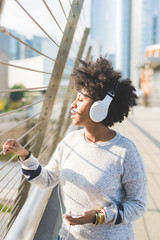 Young beautiful afro woman outdoor in city back light listneing music with head phone and smart phone hand hold, thoughtful - melancholic, music, technology concept