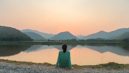 An Asian woman seeing sunset thoughtfully by the lake