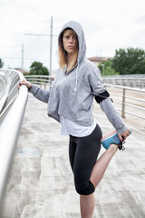 Beautiful young woman does stretching on bridge after hard workout in a spring afternoon