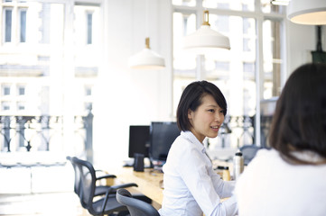 Japanese businesswoman smiling at caucasian colleague in an office