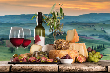 Delicious cheeses with wine on old wooden table.