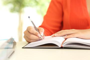 Businesswoman hand writing in agenda