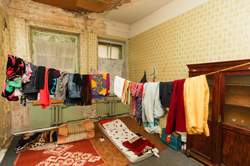 Sleeping area for refugees and refugees' clothes is drying of on the rope in the temporary apartment
