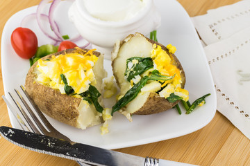 Loaded baked potato with eggs, spinach, cheese.