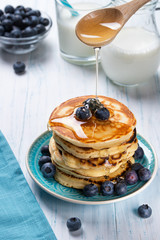 Stack of pancakes with fresh blueberry and honey, healthy breakfast concept