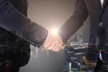 Businessman having a handshake over the city sunlight background