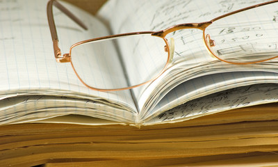 image of notebooks, magazines, glasses  on a table closeup