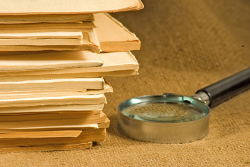 image of notebooks, magazines and magnifying glass on a table close-up
