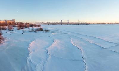 Frozen river Northern Dvina and Railway bridge in Arkhangelsk, Russia. Winter shot.