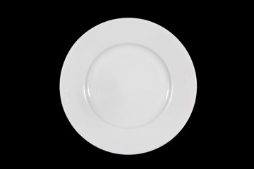 Flat white shallow porcelain plate with wide shoulders on black background directly from above