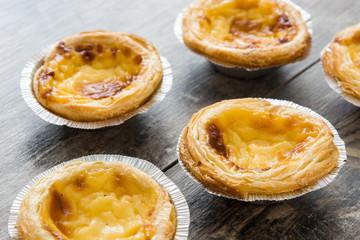 """Pasteis de nata"". Typical Portuguese egg custard tart on wooden background"