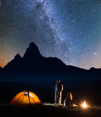 Romantic couple tourists standing together covered with a plaid near campfire and tent at night against mountains background, enjoying starry sky. Beautiful Milky way