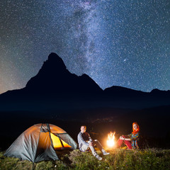 Romantic couple - girl and guy sitting by bonfire and looking to the camera under incredibly beautiful starry sky, Milky way at night camping. In the background silhouette of the mountains. Low light