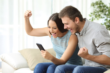 Excited couple watching media in a mobile phone